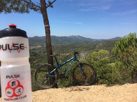 Pulse water bottle resting on the ground in the foreground, bike propped against a tree in the mid-ground near a tree and a bike, with mountains in the background - Paddy Holohan: Tossa De Mar, Costa Brava, posted 28 July 2017