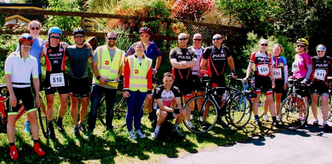 Group picture of cyclists standing beside bikes.